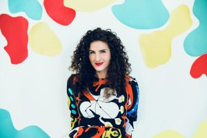 Laila biali in colorful top with multi colored background